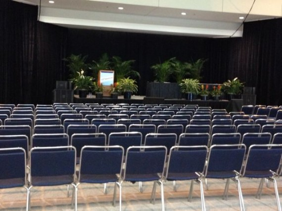 Room setup with hundreds of chairs and a stage