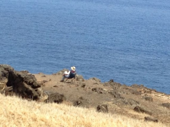 Person sitting on Maui coast overlook