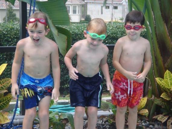 Three five year old boys having fun poolside