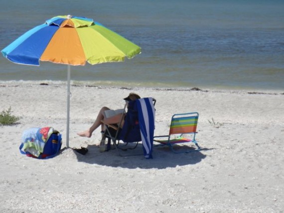 Beach umbrella and tourist on Sanibel beach