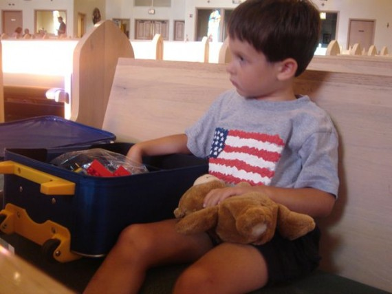 Young boy with teddy bear and suitcase at Church pew