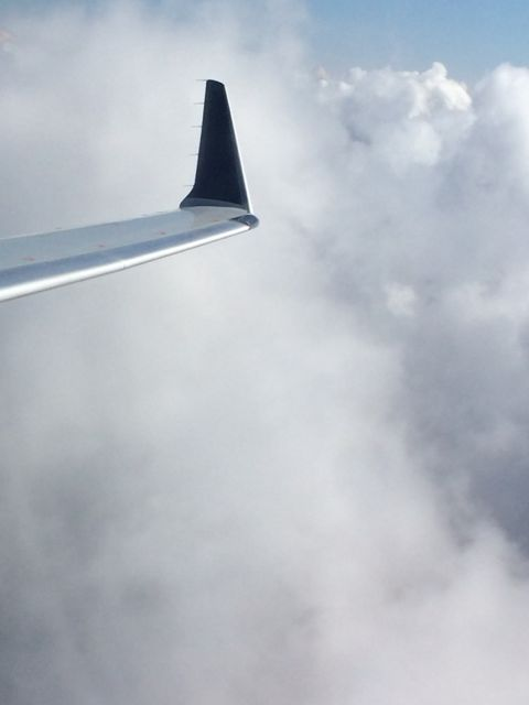 Jet wing against white fluffy clouds