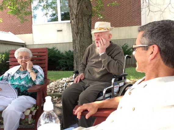 Parents and son sitting in front of Nursing home