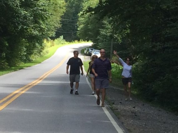 Middle aged group walking along country road