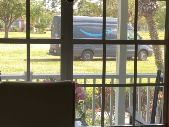 Amazon truck driving across front yard