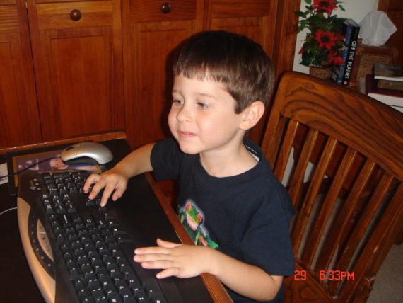 child at computer keyboard