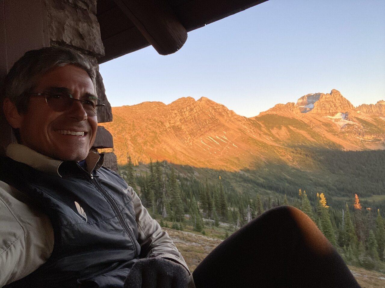 Mountains through chalet window, with jeff noel sitting on window ledge