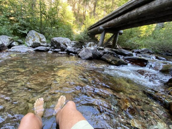 hiker's bare feet soaking in cold stream