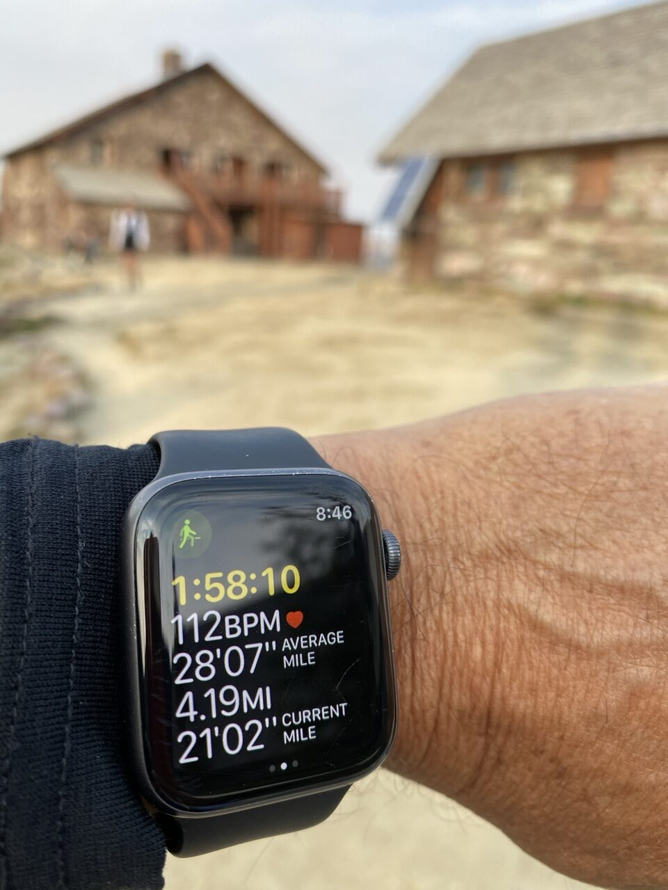 high mountain chalet blurred in background with foreground an Apple Watch screen