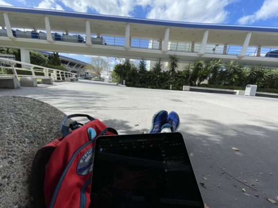 Man sitting on ground off laptop at tomorrowland