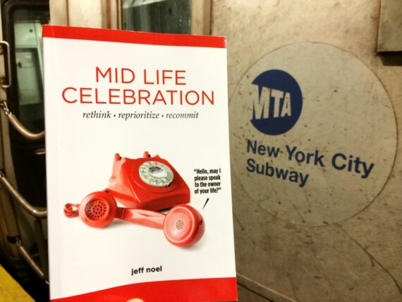 The book Mid Life Celebration Book in the New York City subway