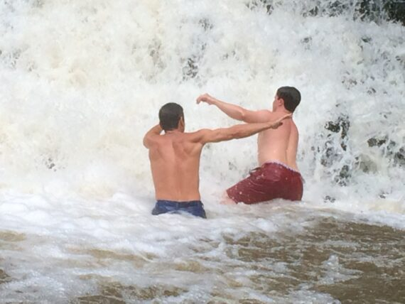 Two shirtless guys at a waterfall