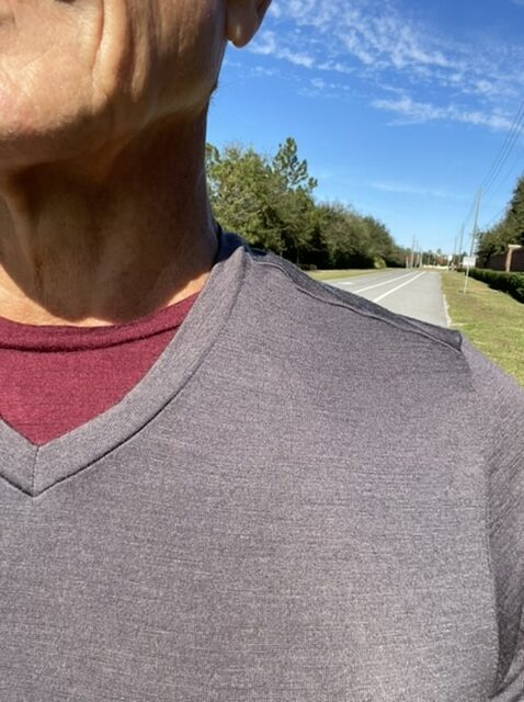 Close up of man wearing two T-shirts walking along the road
