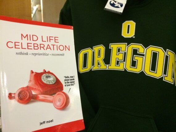 The Book, Mid Life Celebration next to U of Oregon T-shirt