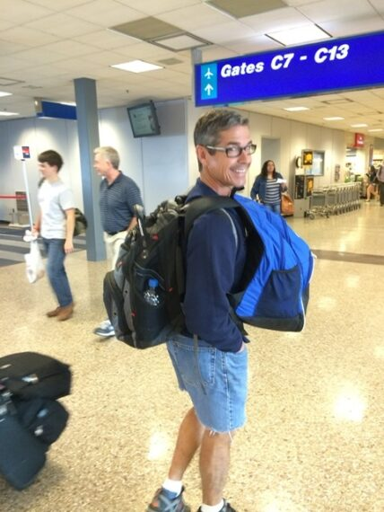 man carrying two backpacks