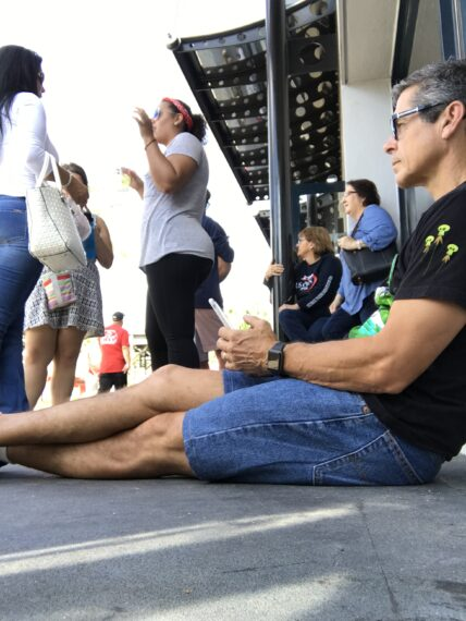man looking at phone sitting on ground at Disney