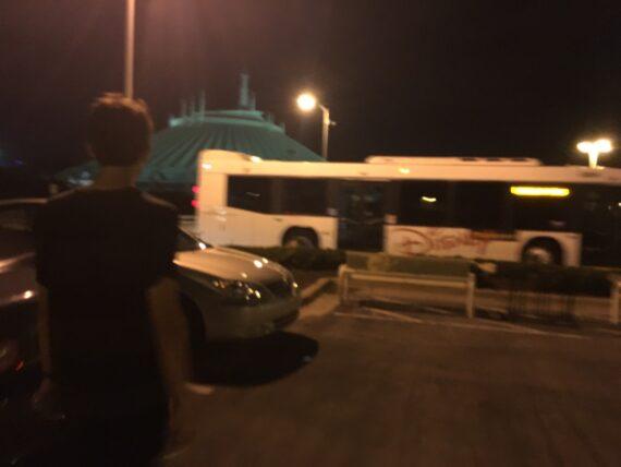 person walking towards Disney bus at night