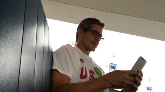 Man using iPhone while traveling on the Tomorrowland Transit Authority's PeopleMover