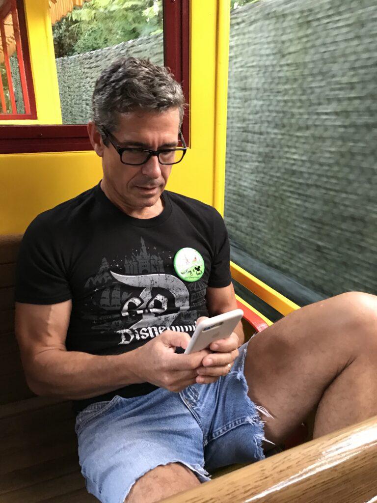 Disney author Jeff Noel writing on iPhone on Disney train