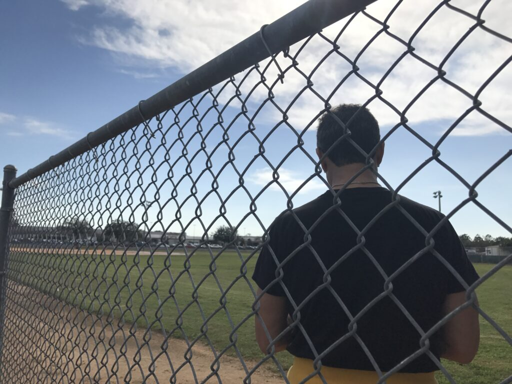 man, with back to camera, sitting next to chain link fence