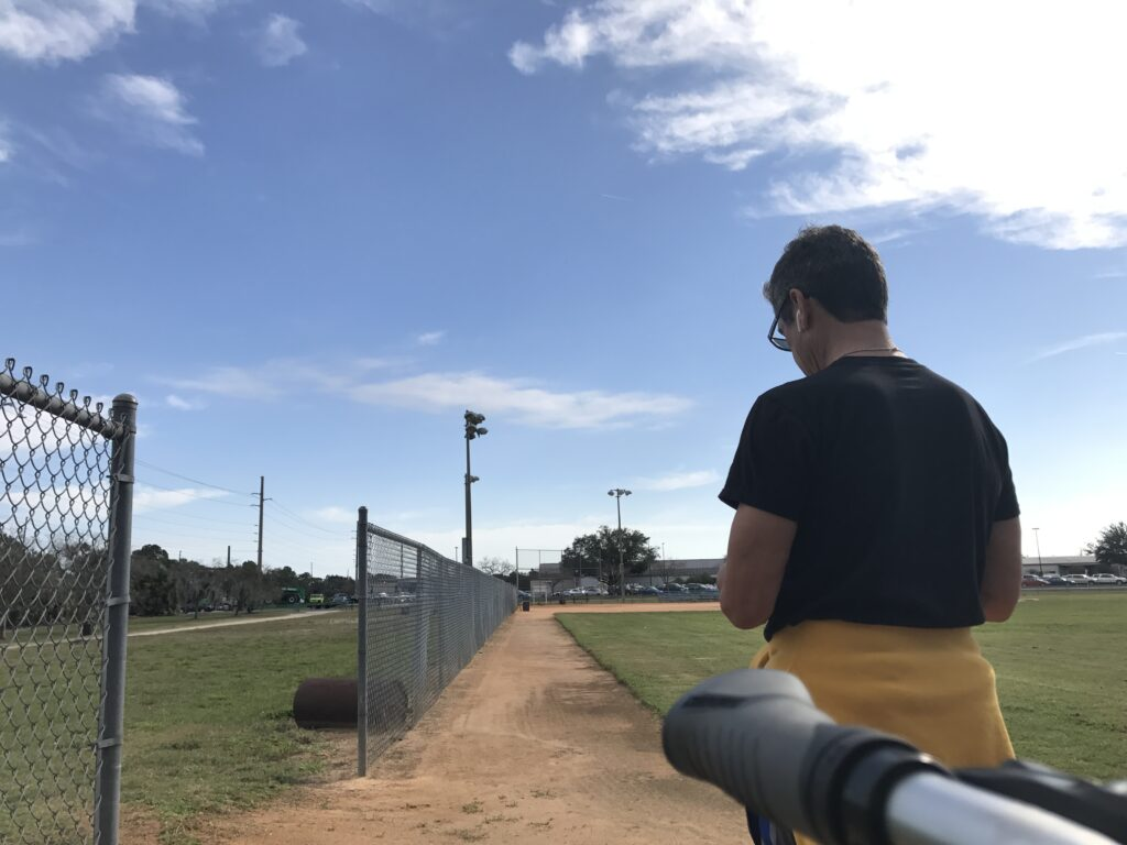 man standing at edge of softball field