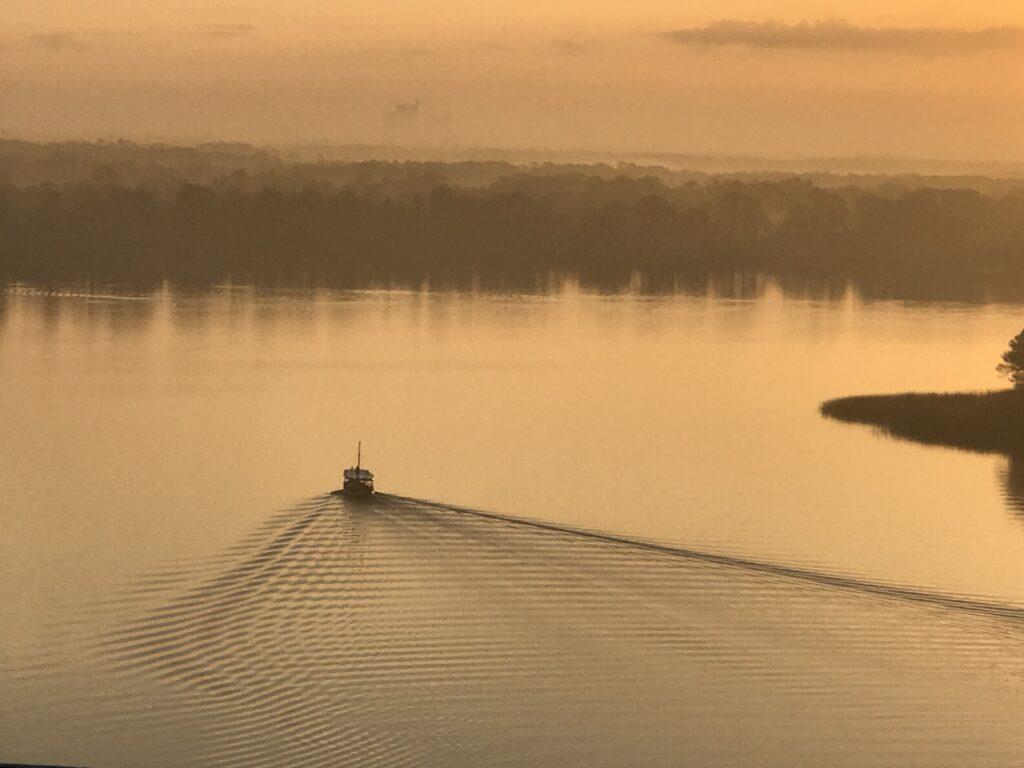 lone boat on still lake at sunrise