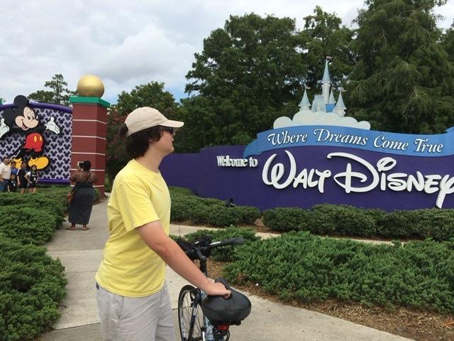 teen with bike at Walt Disney World entrance sign