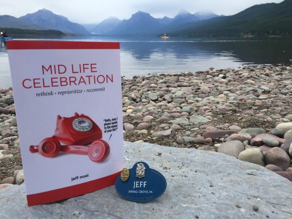 book and Disney name tag on rock at mountain lake shore