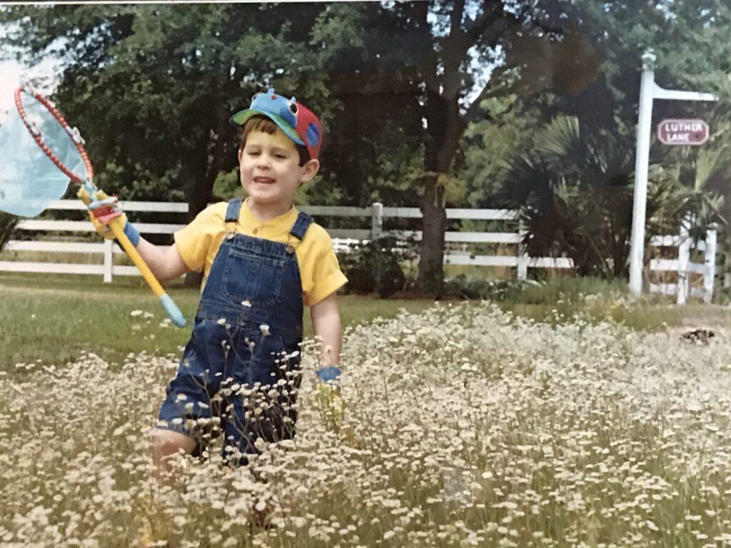 boy in flowers with butterfly net