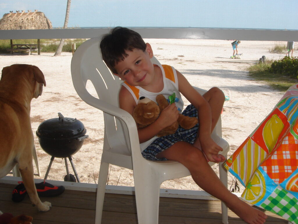 small boy with holding teddy bear with dog sitting nearby